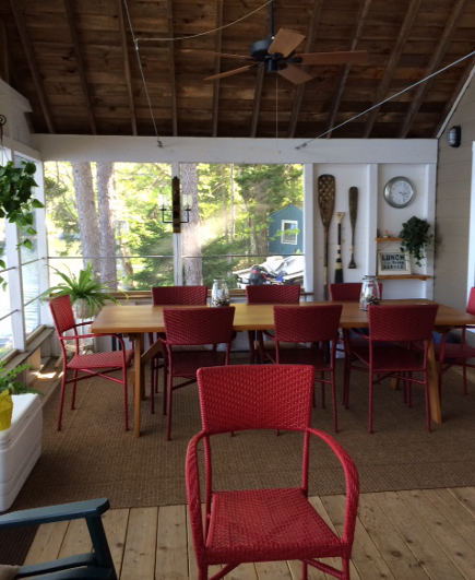 dining area in the screen porch of the Maine Lake Camp - Atticmag