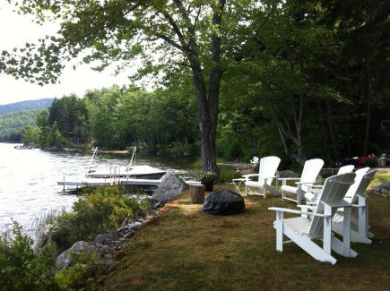 Adirondack chairs around a firepit at the side of the Lake Camp in Maine - Atticmag