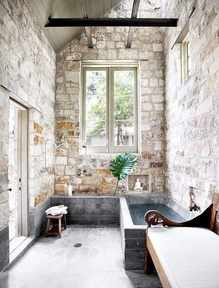 stone wall bath with concrete tub and open shower – Ryann Ford via Atticmag