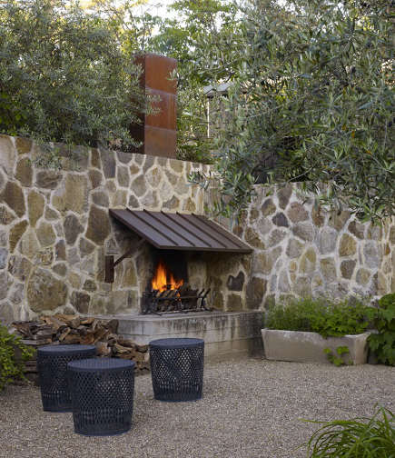 outdoor stone fireplaces - fireplace with steel awning in a wall - roche and roche via atticmag