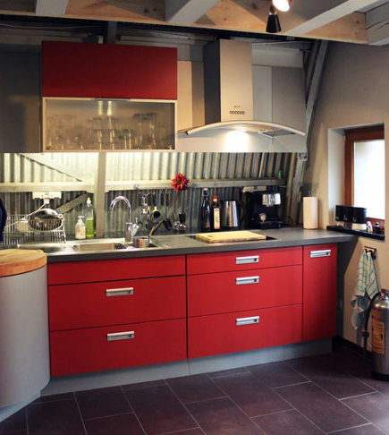 contemporary red kitchens - compact red kitchen in a German aircraft hanger converted into living space - blog.obravip.com via atticmag