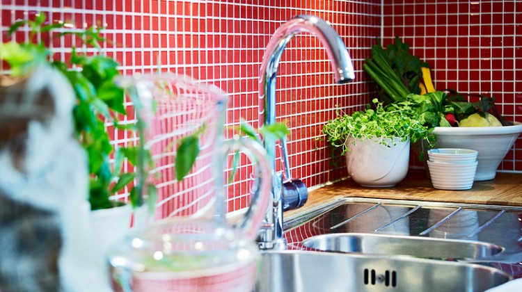 red backsplash in glass mosaic tiles with white grout in a Swedish kitchen - stadshem.se via Atticmag