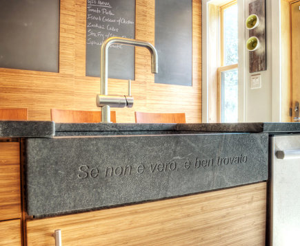 embellished farm sinks - custom gray stone farm sink with phrase engraved on the front - buckminster green via atticmag