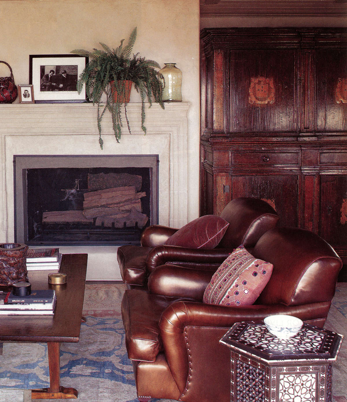 hollywood style - home office seating area with a limestone fireplace and leather chairs in an LA house decorated by Michael S. Smith - H&G via Atticmag
