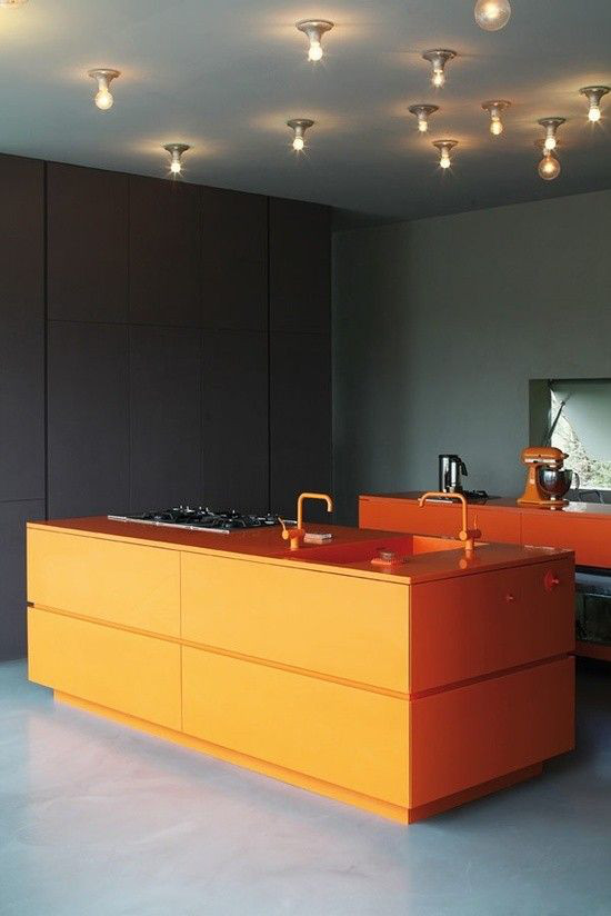 orange kitchens - Dutch minimalist kitchens with orange cabinets and orange Vola faucets, gray floors and walls - vmx architects via atticmag