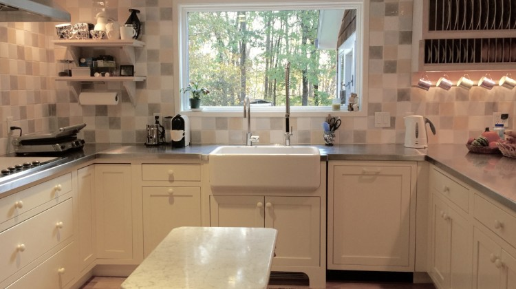 yellow kitchen - sink wall with upmounted Rohl farm sink in bumped out cabinet in the Swedish-inspired kitchen with a glazed tile eurosplash - Atticmag