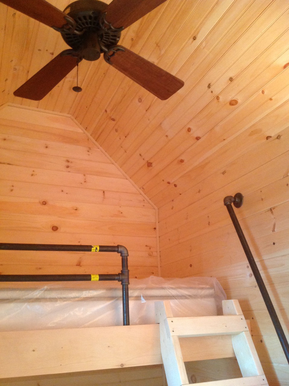 bunkhouse shed - upper twin-bed bunk with plumbing pipe railing and ceiling fan overhead - Atticmag