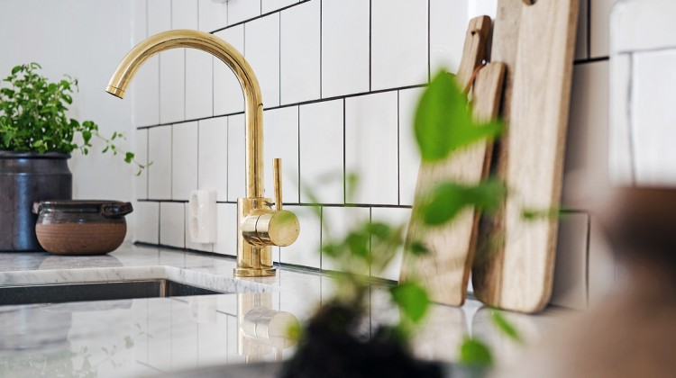brass accent - modern white and gray kitchen with brass faucet and hardware - KuchniAremont via Atticmag