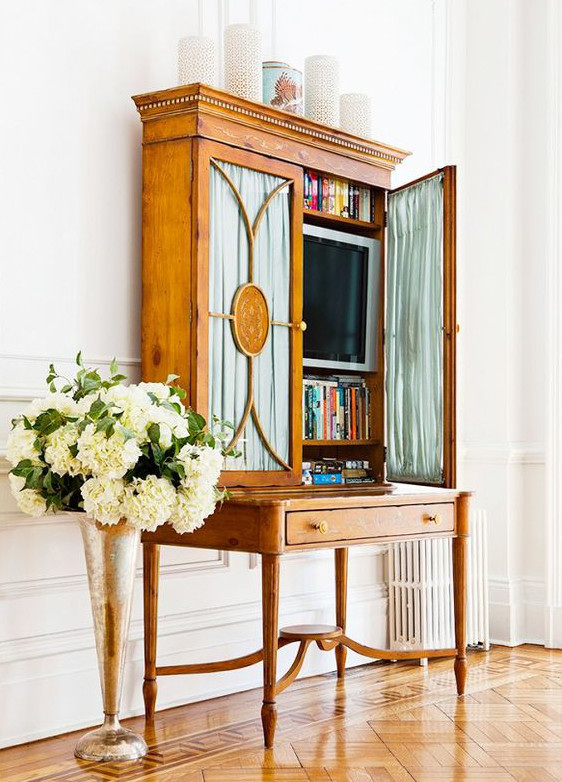 hidden tvs - tv behind shirred curtains on the glass doors of a Directoire style library desk cabinet - Domaine Home via Atticmag