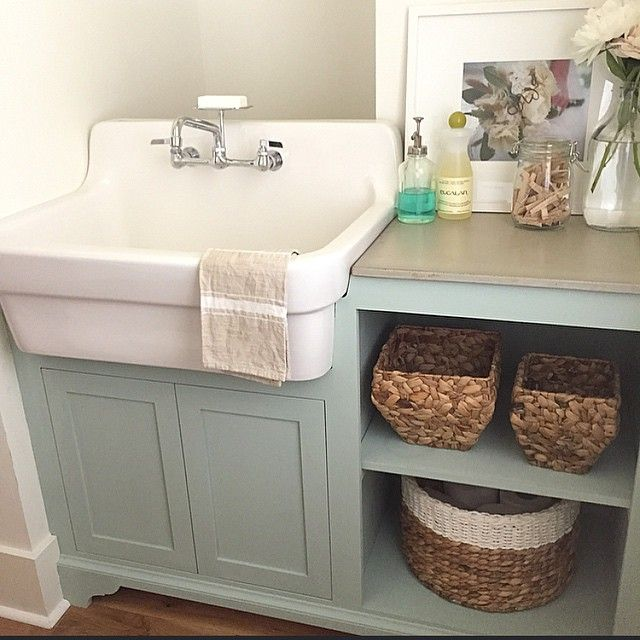 laundry room sink - American Standard sink in a specially cut out base cabinet painted in Credenza green Amy Howard Milk paint - Instagram via Atticmag