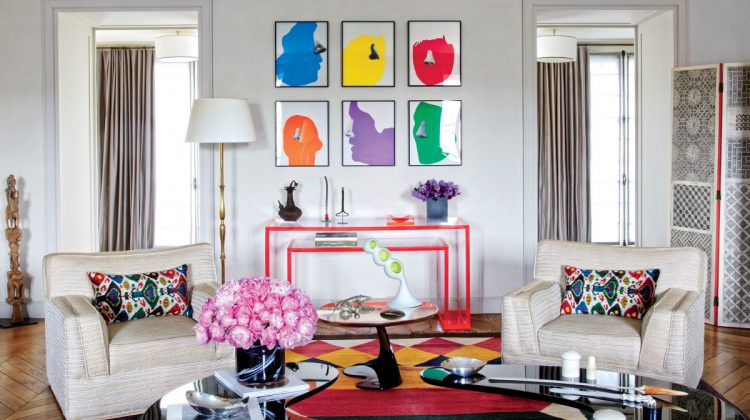 color picture wall - six different colored John Baldessari images, in black frames, are displayed above a red-edged lucite Alexandra von Furstenberg console table in the Paris apartment of fashion designer Veronica Toub. The table supports the color in the art above it - AD via Atticmag