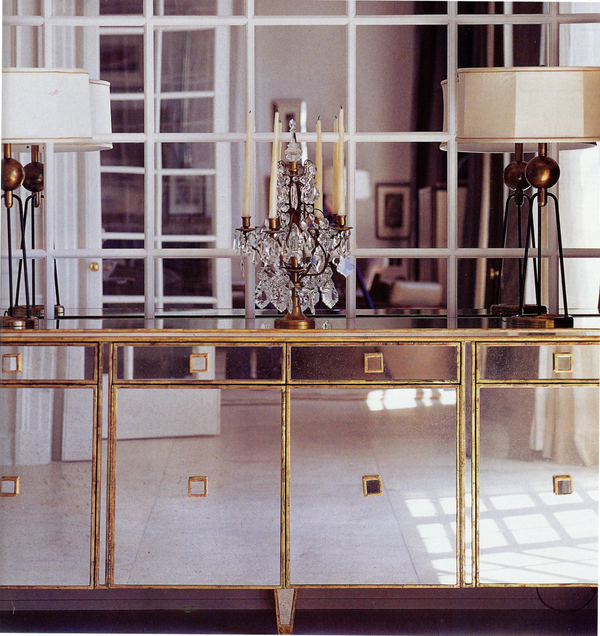 mirror on mirror - mid-century dining room with a gilt and mirror custom buffet against a divided lite mirrored wall - Met Home via Atticmag