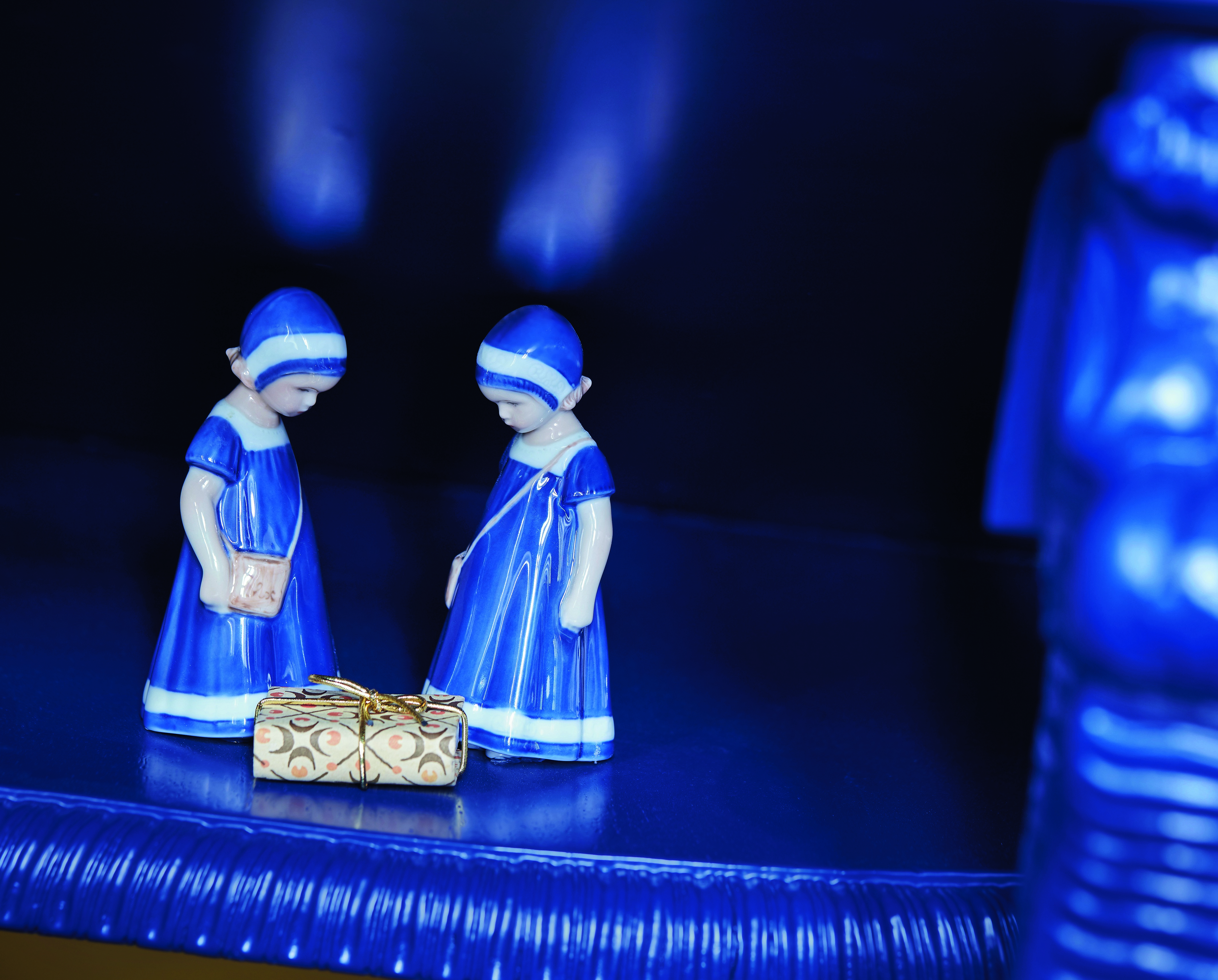 fashionable Christmas - a deconstructed cobalt blue Christmas table by Baum & Pferdgarten has two tiny figurines in cobalt blue and whit dresses contemplating a Christmas gift - Royal Copenhagen via Atticmag