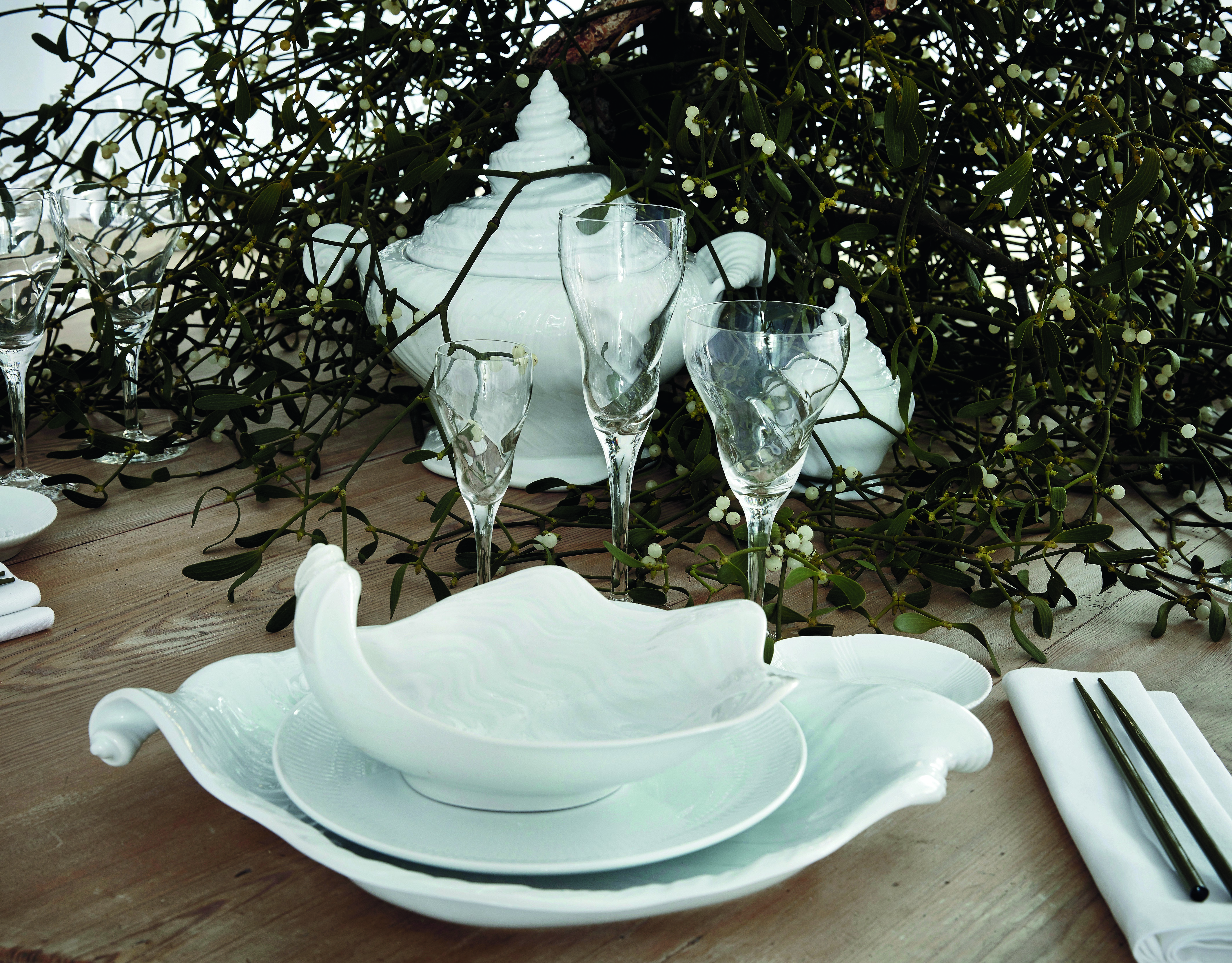 fashionable Christmas - Mark Tan's traditional Scandinavia table with natural greenery takes and tiny lights on a dramatic organic white-on-white affect with Arje Griegst's Conch series dishware - Royal Copenhagen via Atticmag