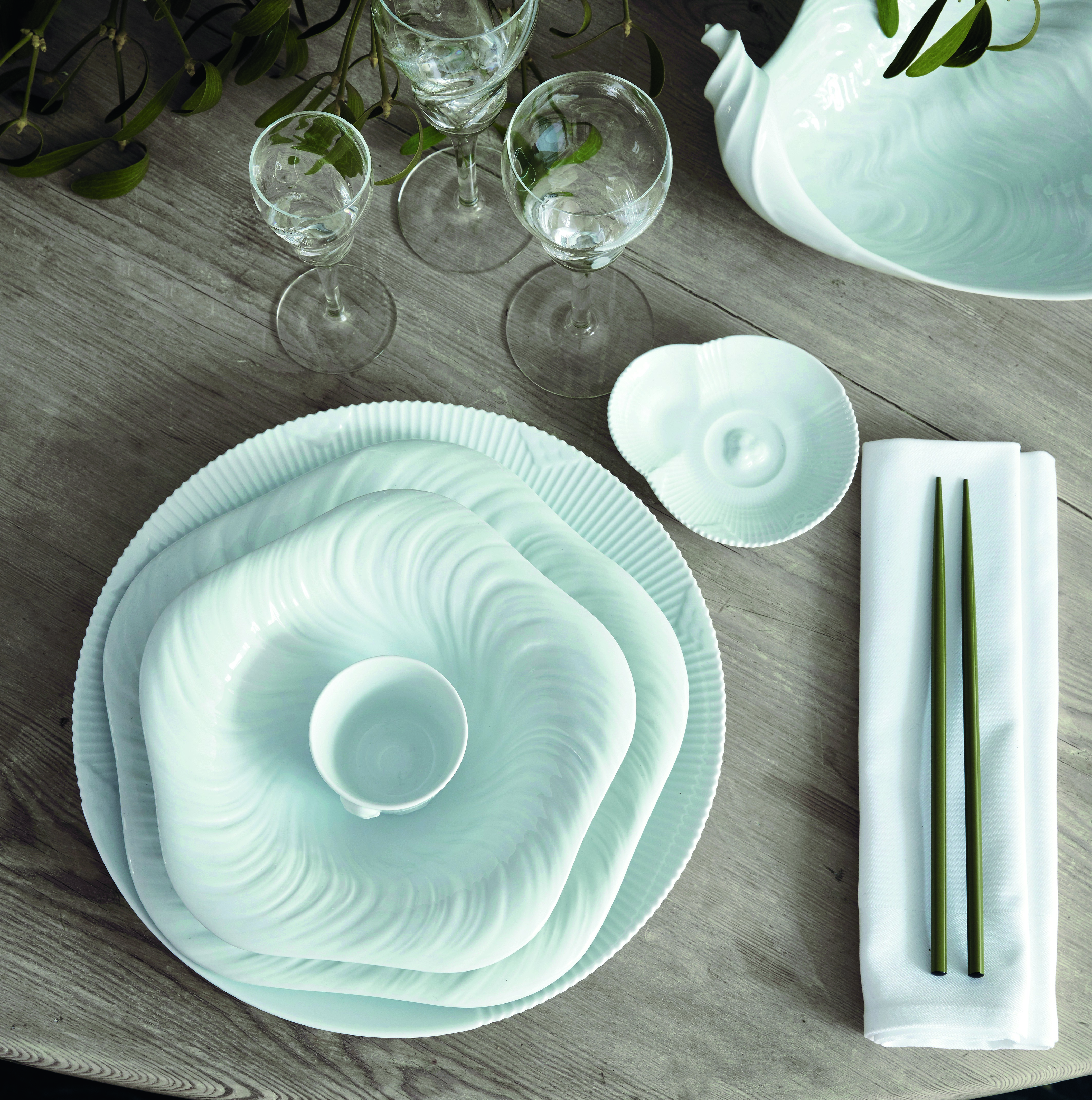 fashionable Christmas - Mark Tan's traditional Scandinavia table with natural greenery takes on a dramatic organic white-on-white affect with Arje Griegst's Conch series dishware - Royal Copenhagen via Atticmag
