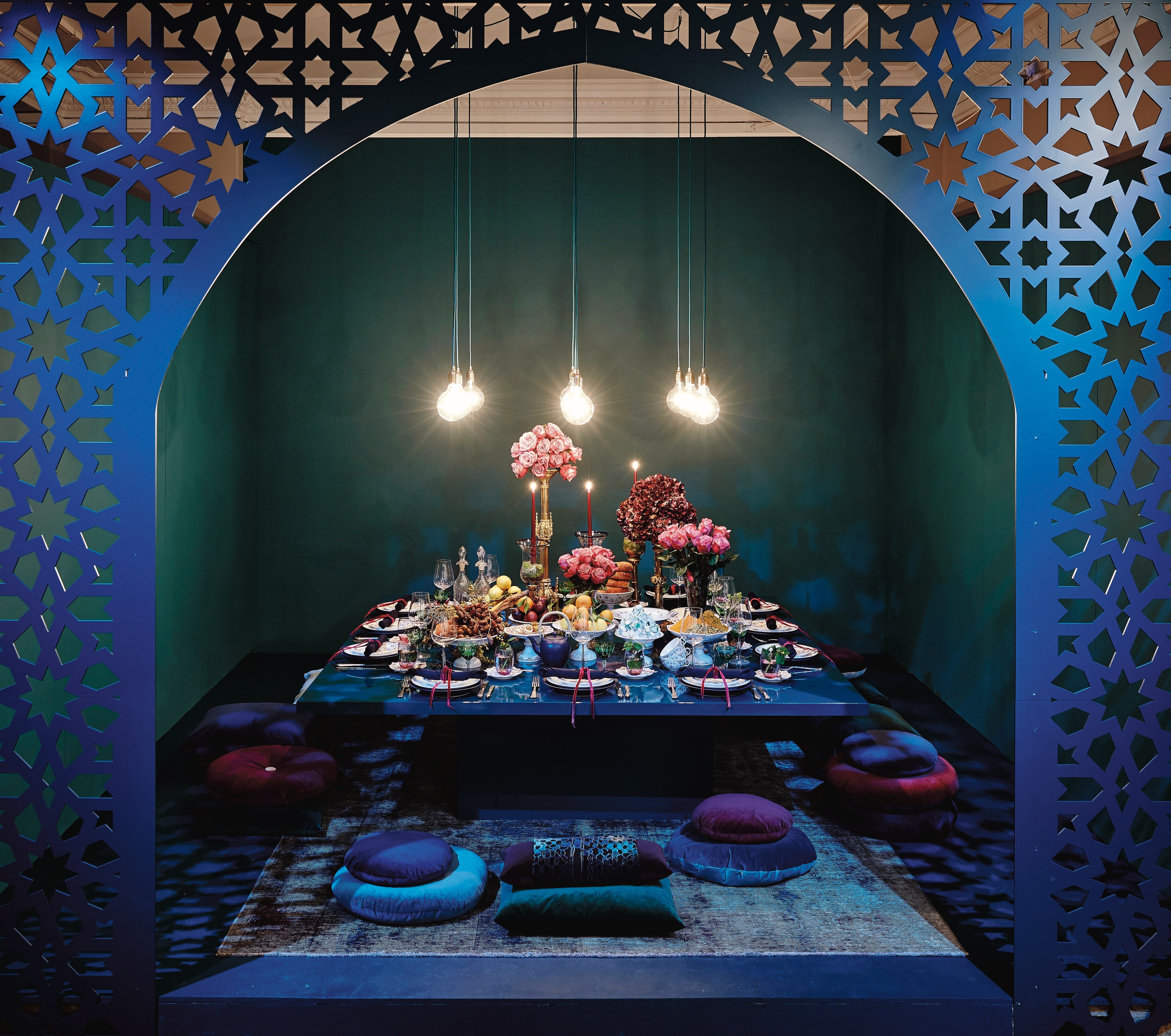 fashionable Christmas - a Middle Eastern-inspired table by Leyla Piedayesh combines midnight colors with lush displays of flowers and plates of fruit using Blue Fluted and Half Lace Purpur china on a low table behind a Moorish-style screen - Royal Copenhagen via Atticmag