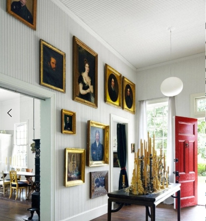 grand picture wall - an oil portrait picture wall in the foyer of Federico de Vera's house, a converted railway station in Amenia, New York - Elle Décor via Atticmag