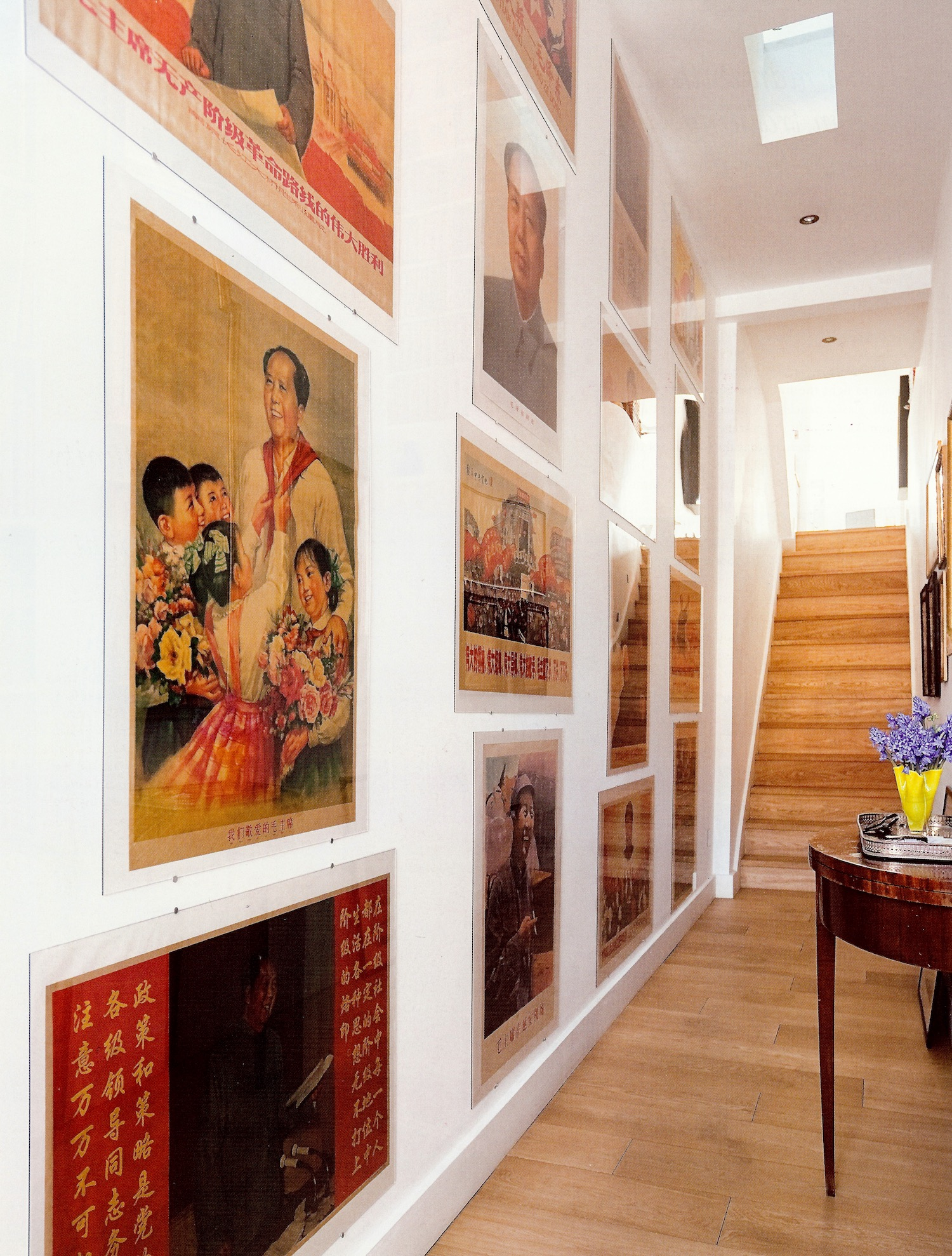 grand picture walls - hallway of a London flat hung with a collection of Chinese Mao posters - House & Garden via Atticmag