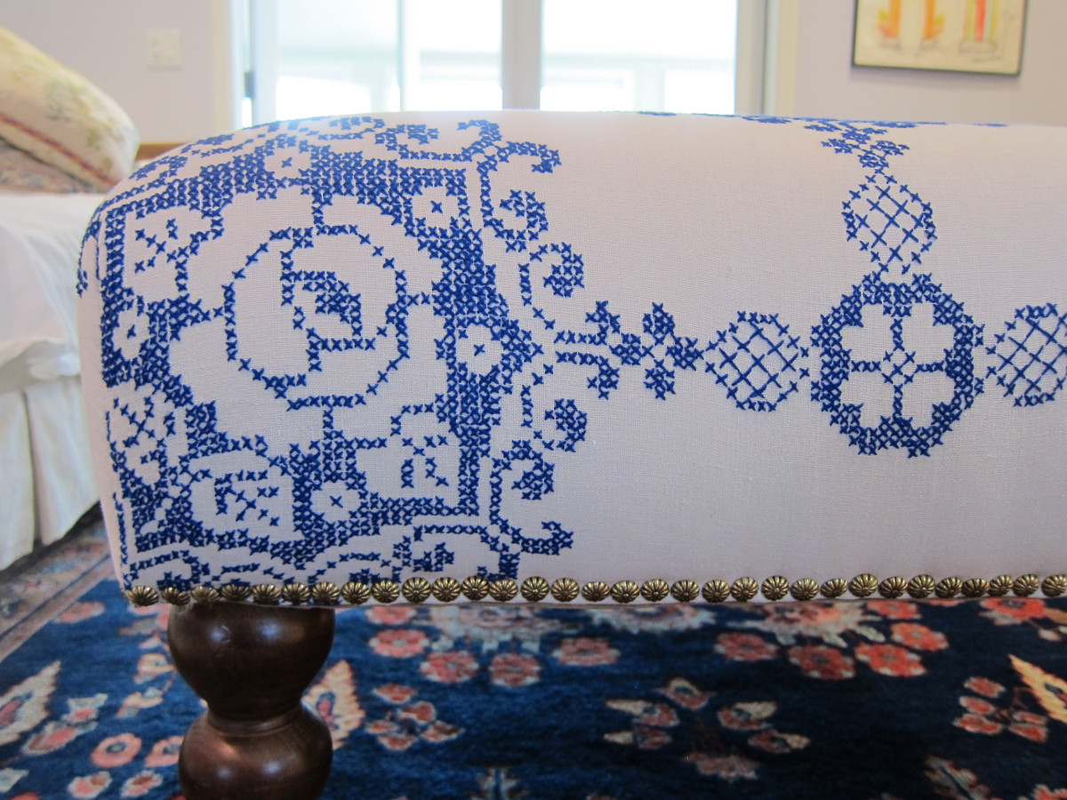 embroidered vintage tablecloth repurposed as an ottoman cover - Atticmag