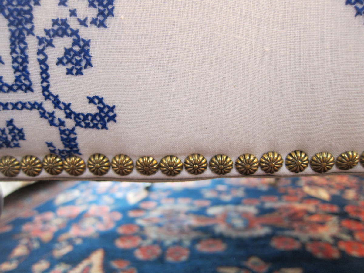 detail of ottoman reupholstered with an embroidered vintage tablecloth and finished with melon head brass tacks - Atticmag
