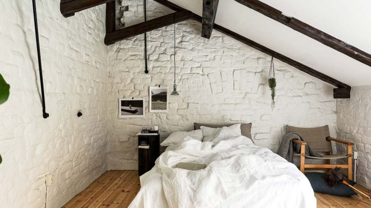 black accents on ceiling beams and supports add contrast to a rustic cream-colored bedroom - skonahem via atticmag
