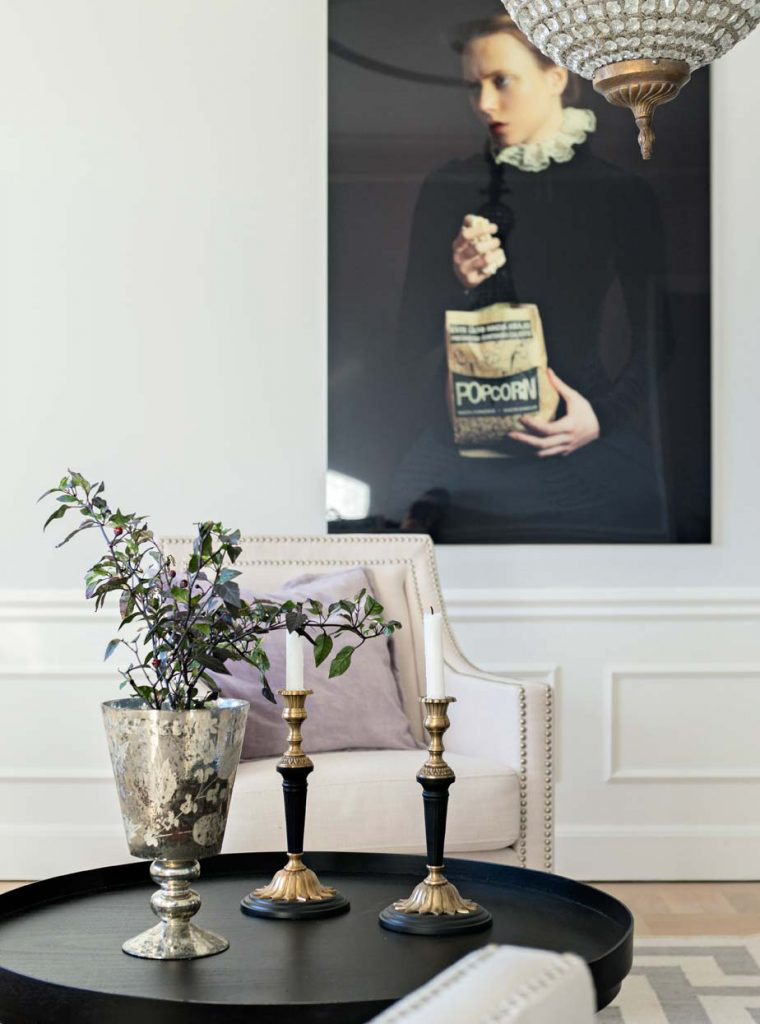 black accents in a quirky art-size photo coordinate well in a living room with an ebonized side table and candlesticks - skonahem via Atticmag