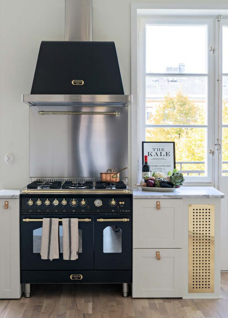 black accents in a stark white Swedish kitchen are provided by the Lofra Dolcevita 90 black range and hood - skonahem via Atticmag
