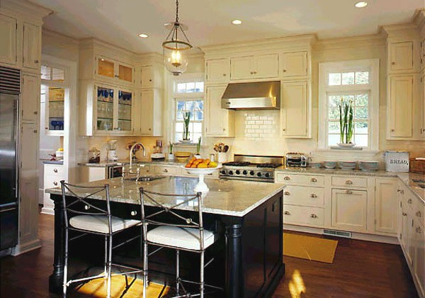 old world kitchen with black island, white kitchen cabinets and neutral granite - via Atticmag