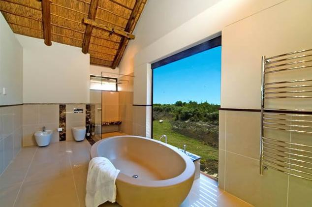 monochromatic modern bath in a south african rental villa with large picture window - my holiday rental via Atticmag
