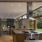 glass wall kitchen - minimalist kitchen with a glass wall on one side and double island - bohlin cywinski jackson via Atticmag