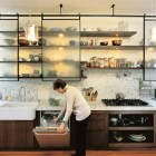 renovated modern kitchen with storage over a carrara marble backsplash - Dwell via Atticmag