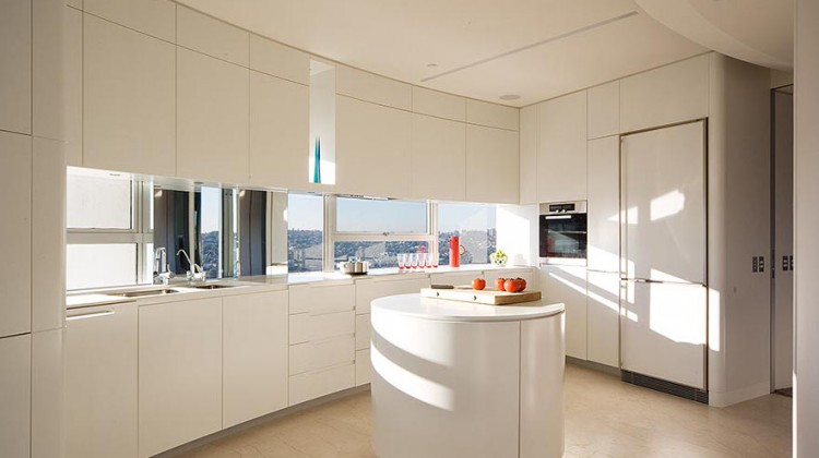 Modernist apartment panorama kitchen with a round island on a pedestal and views from a curving windows in the backsplash - Stanic Harding via Atticmag