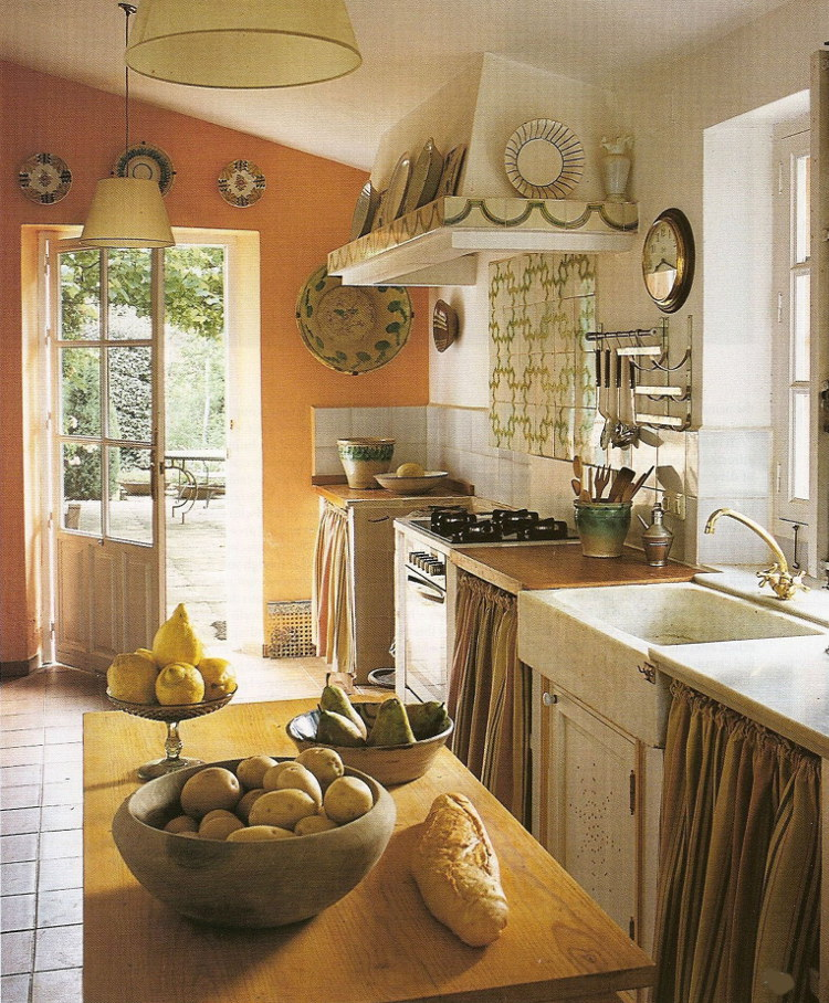 spanish country kitchen - rustic kitchen with farm sink, sunny wall color and fabric over lower shelves - World of Interiors via Atticmag