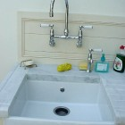 small farm sink used in a pantry with wall-mounted faucet and cold water tap - Robinson & Cornish via Atticmag