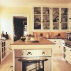 oven in island - white Long Island kitchen with black counters and a wall oven in one end of the island - Saveur via Atticmag
