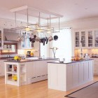 pot rack - white kitchen with double islands, a giant pot rack and a mirror behind the range - Crown Point via Atticmag