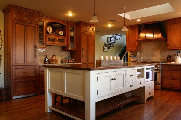 glazed cherry cabinets with matching paneled refrigerator and freezer plus antique white island with built in microwave - crown point kitchen cabinets via atticmag