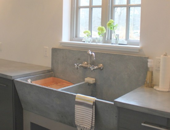 slate farm sink with angled front and integral back on a table-style base in a kitchen - molly frey design via atticmag