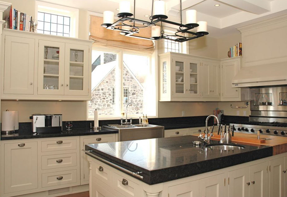 wood burning oven - large black and white kitchen with appliances galore plus a pizza oven - Scott Yetman via Atticmag