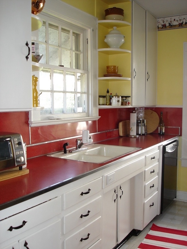 red kitchen accents - vintage 1950s red laminate counter and backsplash in an original kitchen - via Atticmag