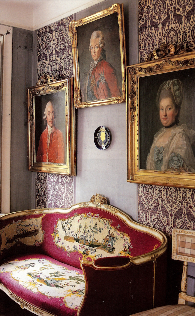 picture wall ideas - Swedish picture wall with antique portraits hung over fabric - WOI via Atticmag