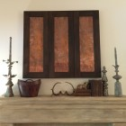 tv over the fireplace concealed behind sliding copper panels