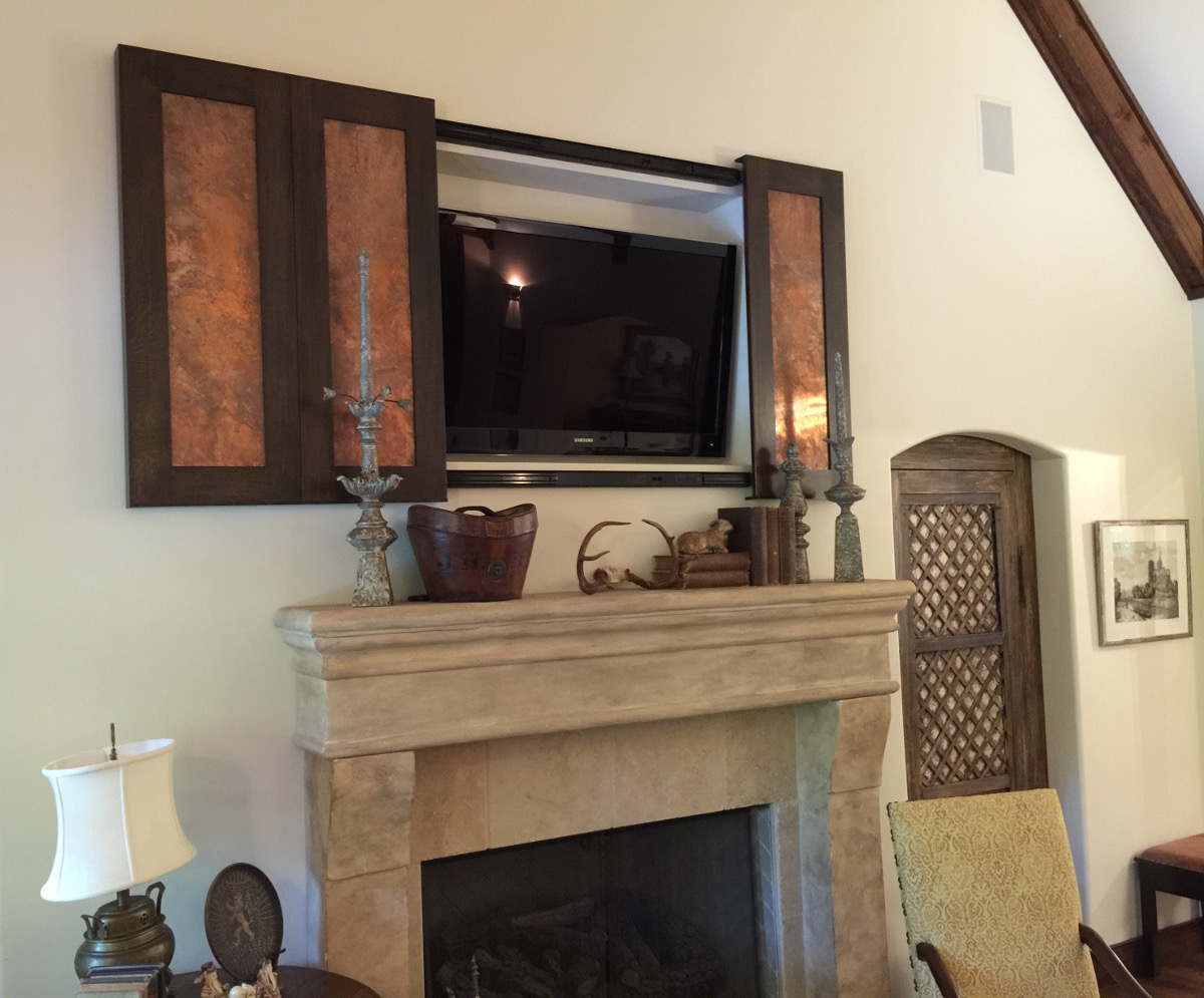 tv above the fireplace with copper panels open to reveal the screen - atticmag