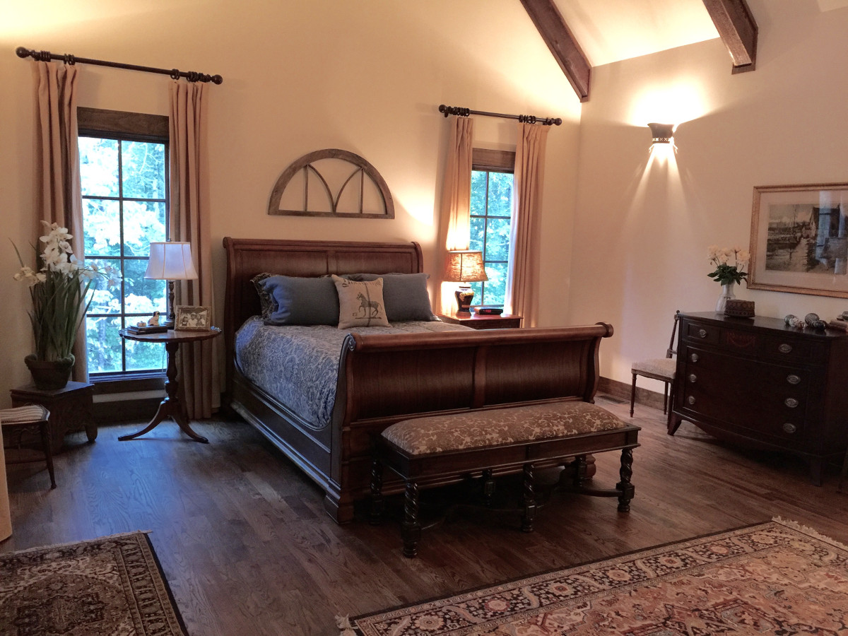 alabama stone cottage - vintage arched window frame over walnut sleigh bed in master bedroom - atticmag