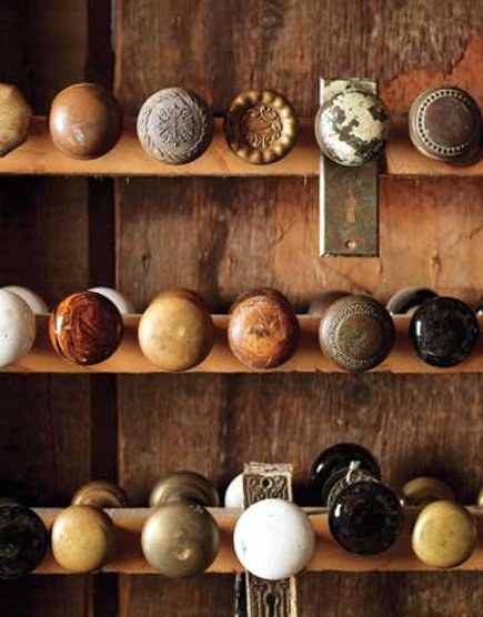 vintage collections - doorknobs displayed in a wood niche - Country Living via Atticmag