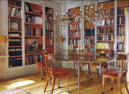 dining room bookcase - dining with two bookcase walls and double chandeliers - WOI via Atticmag