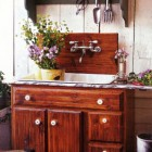 gardener's sink with faucet mounted on the wall over a wooden backsplash