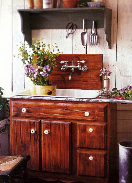 gardener's sink with wall-mount sink faucet over a wooden backsplash - Homemag via Atticmag