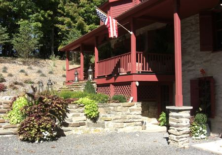 stone houses in Ulster County, NY in the Catskill Mountains - front entry of a house with dark red trim- Atticmag