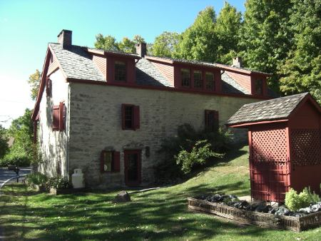 stone houses in Ulster County, NY in the Catskill Mountains - rear view of house with dark red trim from the street - Atticmag